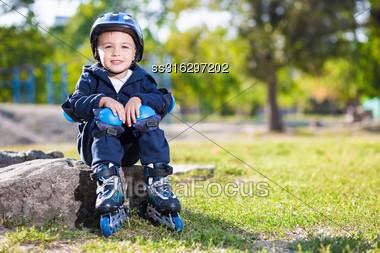 Cute Little Skater Boy Sitting On The Stone In The Park Stock Photo