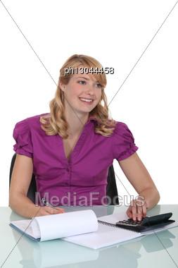 Cute Secretary All Smiles Using Calculator Stock Photo