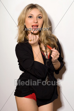 Cute Young Blond Woman With Lipstick In Hand Stock Photo