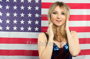 Cute Young Blonde On A Background Of The American Flag Stock Photo
