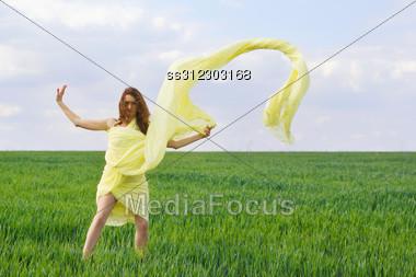 Cute Young Woman Dancing In A Green Field Stock Photo