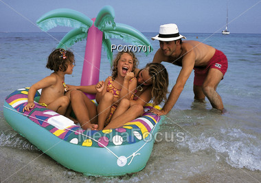 Dad pushing his kids on a float at the beach Stock Photo