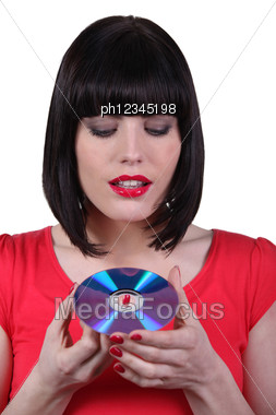 Dark -haired Woman Holding Compact Disc In Hands Stock Photo