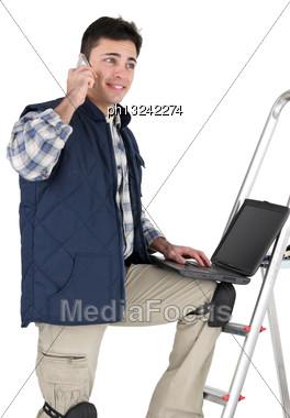 Decorator Making Telephone Call Whilst Using Laptop Stock Photo
