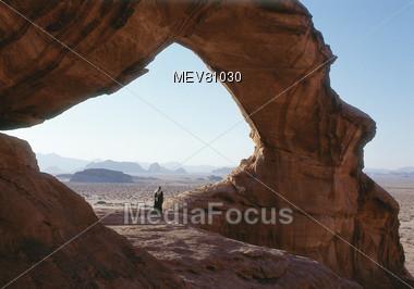 Desert Bedouin Under Rock Arch, Jordan Stock Photo