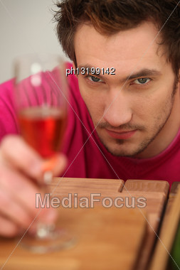 Determined Man Looking At A Wine Glass Stock Photo