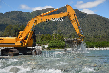 Digger Shifting Shingle To Deepen The Channel In A Flowing River, Westland, New Zealand Stock Photo