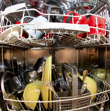 Dishwasher With Dirty Dishes In Kitchen Stock Photo