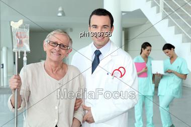 Doctor Helping His Patient Walk Stock Photo