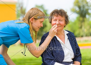 Doctor Nursing Old Woman With Nose Drop Because Of Ragweed Allergy And Flu Stock Photo