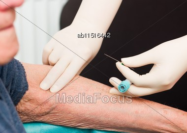 Doctor Searching For Elderly Patient's Vein For Taking Blood For Lab Tests Stock Photo