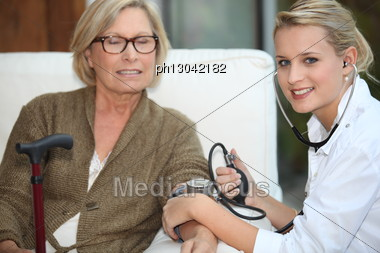 Doctor Taking Her Patient Blood Pressure. Stock Photo