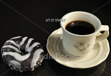 Donut And Cup Of Coffee On Black Background Stock Photo