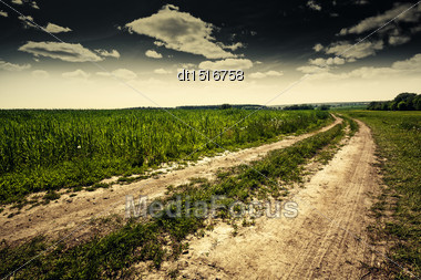 Dramatic Landscape With Empty Road Through The Meadow Stock Photo