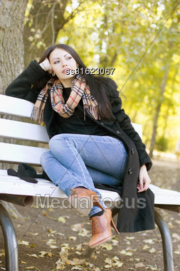 Dreamy Young Brunette Sitting On A Bench In Autumn Park Stock Photo
