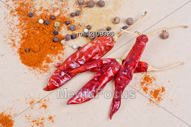 Dried Peppers And Other Kind Of Peppers Spices On A Brown Background Stock Photo