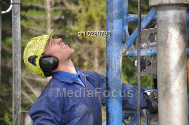 Drilling Crewman Looking Up At The Top Of The Drilling Rig Stock Photo