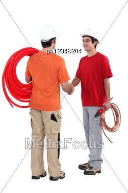 Duo Of Plumbers Shaking Hands Stock Photo