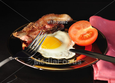 Egg And Bacon On Black Background Stock Photo