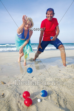 Elderly Couple Playing Bocce Ball On The Beach Stock Photo