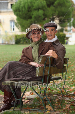 Elderly Couple Sat On Bench Stock Photo