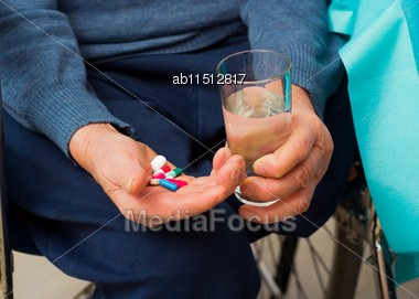 Elderly Disabled Man Taking Daily Medicine Stock Photo