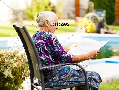 Elderly Lady Reading Newspaper Peacefully In Her Beautiful Garden Stock Photo