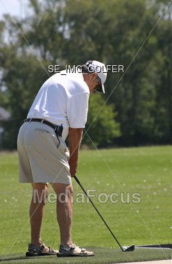 An elderly man practicing his golfing game Stock Photo