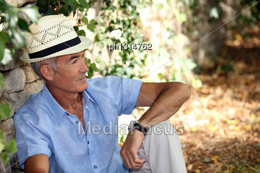 Elderly Man Sitting Against The Stone Wall Stock Photo