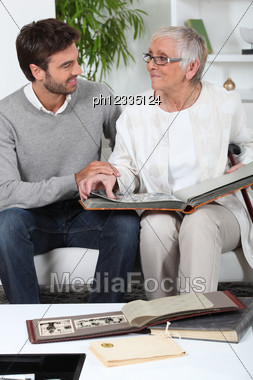 Elderly Person Looking At Photos With Son Stock Photo