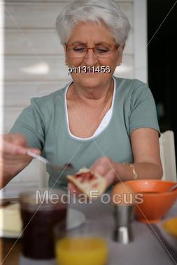 Elderly Woman Eating Balanced Breakfast Stock Photo