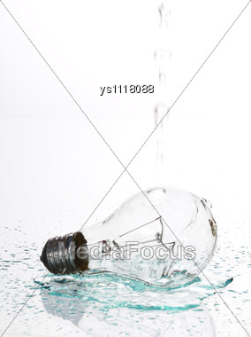 Electric Bulb Lays On A Table And On Her To Pour Water Stock Photo
