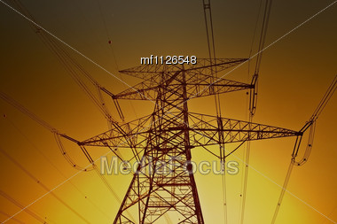 Electric Power Lines On The Golden Sky Background Stock Photo
