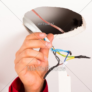 Electrician Assembling Power Supply For Ceiling Illumination Stock Photo