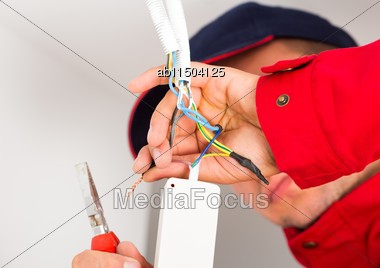 Electrician Installing Power Supply On Wires Hanging Out From Flexible Tube Stock Photo