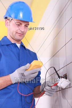 Electrician Is Checking An Outlet With An Ammeter Stock Photo