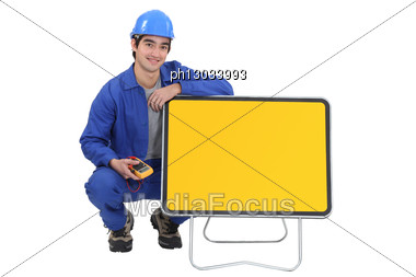 Electrician Kneeled Next To A Blank Road Sign. Stock Photo