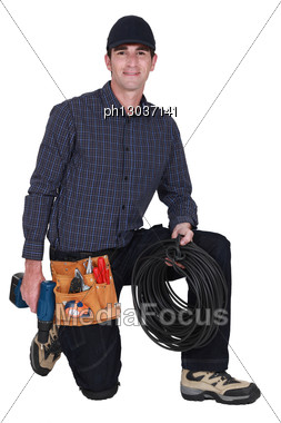 Electrician Kneeling With Drill And Cable Stock Photo