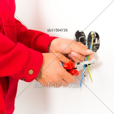 Electrician Working With Wires, Mounting New Electrical Outlet Stock Photo