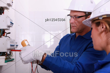 Electricians Fitting A Fusebox Stock Photo