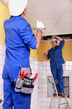 Electricians Wiring A Large Room Stock Photo