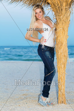 Elegant Blond Woman Posing In Casual Clothes Near A Palm Stock Photo