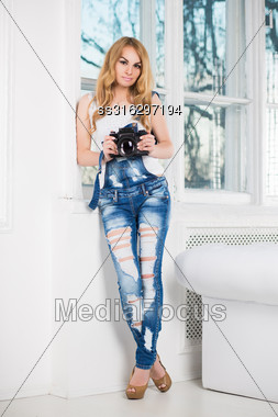 Elegant Blond Woman Wearing Ragged Denim Overalls Posing With Camera Stock Photo