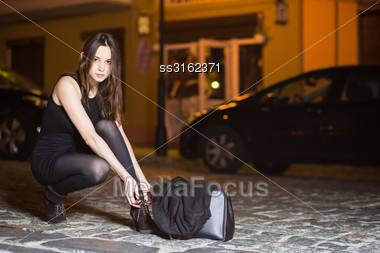 Elegant Young Brunette Wearing Black Dress Sitting Near The Road Stock Photo