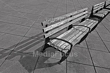 Empty Park Benches Over A Cement Tiles With A Shadow Stock Photo