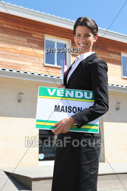 Estate Agent With A Vendu Sign Stock Photo