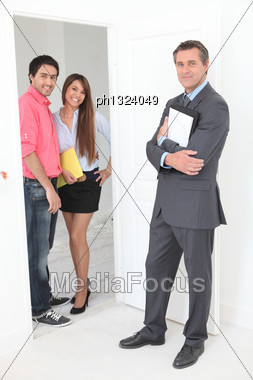 Estate Agent With Young Couple Stock Photo