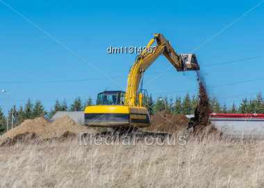 Excavator Machine Works At Construction Site Stock Photo