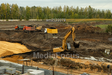 Excavator Pours Soil Into The Back Of The Truck Stock Photo