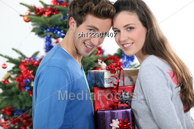 Excited Young Couple Stood By The Christmas Tree Stock Photo